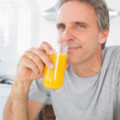 Man drinking orange juice. Do Vitamin C supplements cure colds? Cooper Complete Nutritional Supplements answers